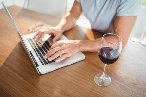 man working on laptop and a glass of wine on the table